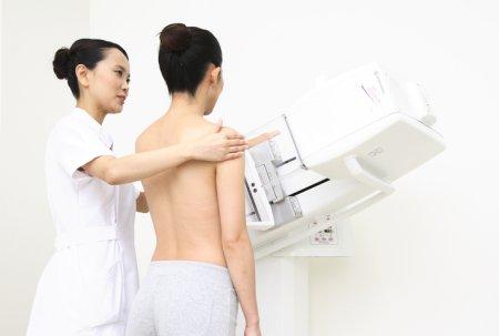 検査機器の圧迫板で乳房を挟みます
